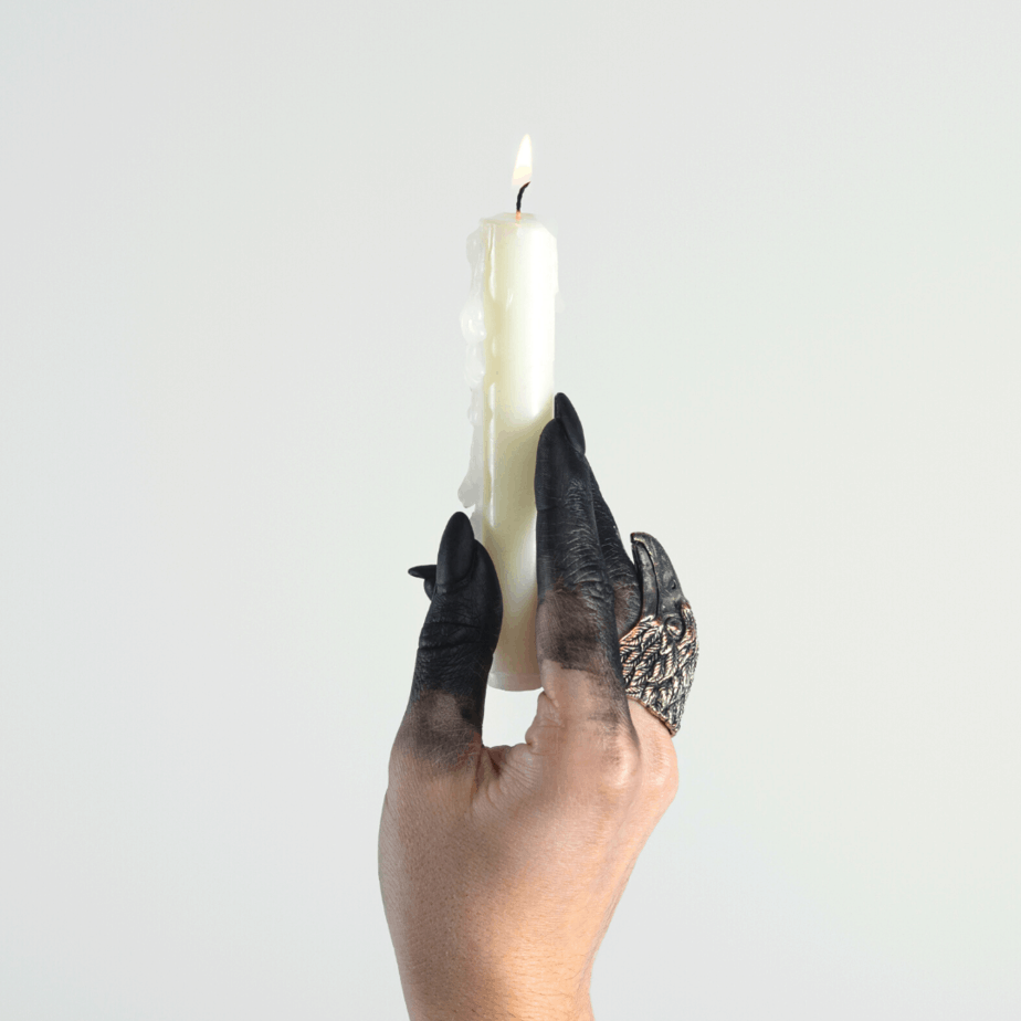 A witchy hand with scorched black fingers holding a white candle for Imbolc