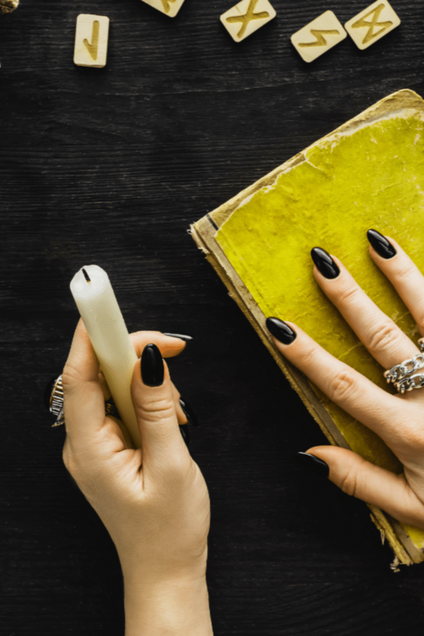 A witch with black nails and chain rings with a hand on her book of shadows and holding a white candle on a black wood table.