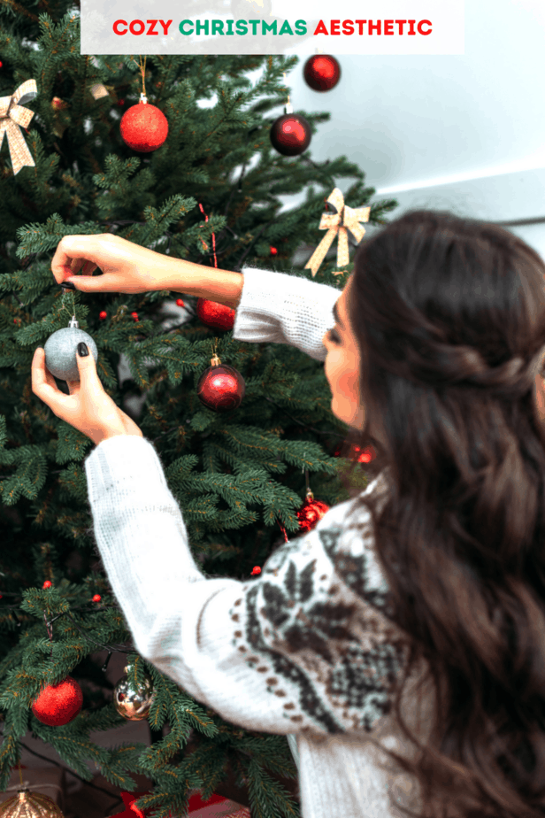 A woman putting hygge Christmas bulbs on her cozy Christmas tree