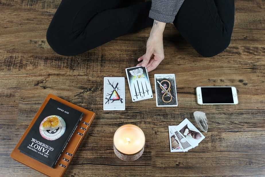 Woman sitting on wooden floor with tarot card spread, reading her fortune surrounded by candle burning, phone, photos and notebook. Eastern philosophy, alternative worship at an altar of sorts.