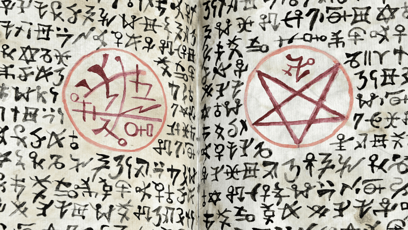 The Theban alphabet and other cipher systems in a witch's book of shadows with a red pentagram and a sigil